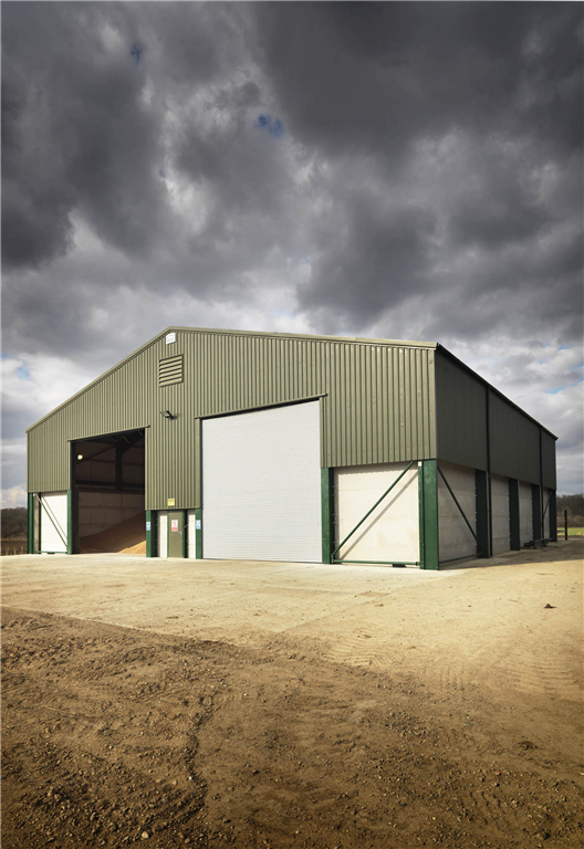 A 2000 tonne grain store built in partnership with Ben Burgess, Norfolk. Steel portal frame, fibre-cement roof, metal wall cladding, concrete grain walls, galvanised roller doors & personnel doors. Gallery Image