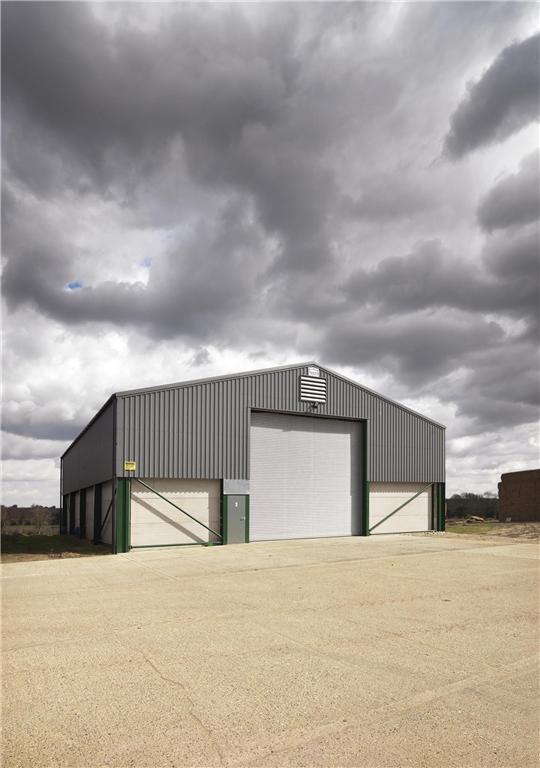 Our standard 1000 tonne grain store. Steel portal frame, fibre-cement roof, metal wall cladding, concrete grain walls, galvanised roller doors & personnel door. Call Agri Sales on 01953 850611. Gallery Image