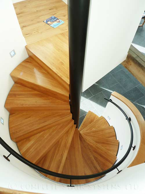 Bespoke Spiral Stair, enclosed balustrade, with boxed oak treads and powder coated steel handrail. Gallery Image