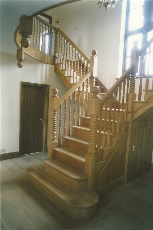 A feature staircase handmade by craftsmen in English Oak, featuring barley sugar twist balusters in the design. Gallery Image