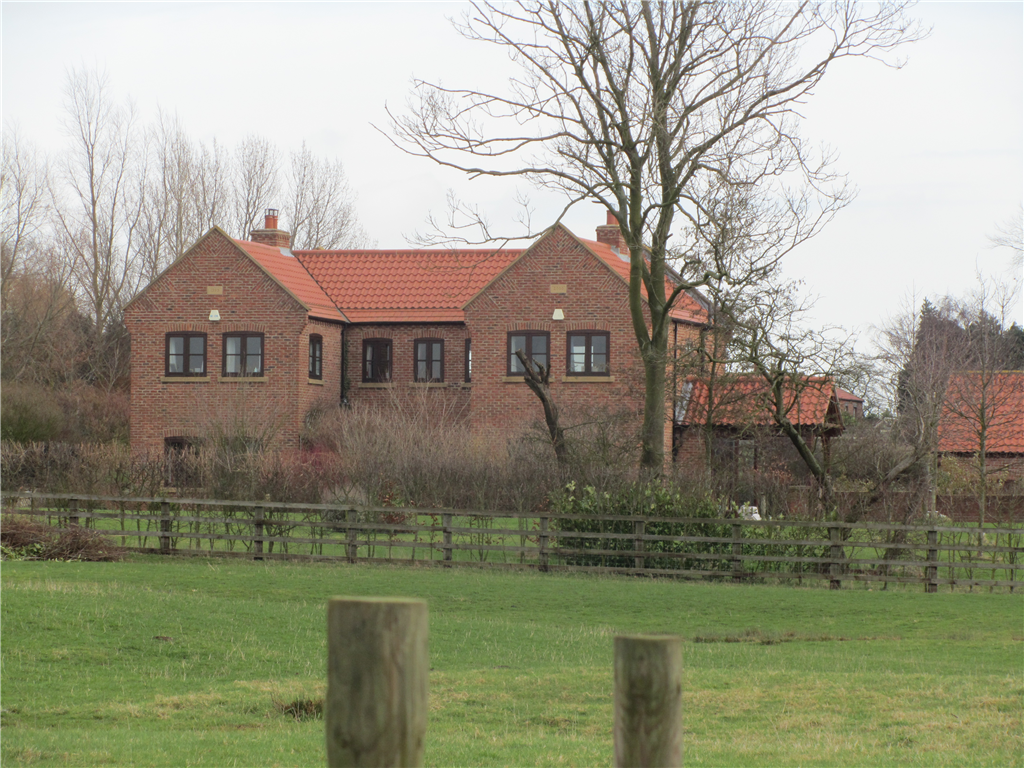 A rural replacement dwelling in handmade brickwork under a pantiled and plain clay tiles pitched roof, adjacent to stables.  Gallery Image