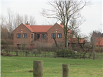 A rural replacement dwelling in handmade brickwork under a pantiled and plain clay tiles pitched roof, adjacent to stables.  Gallery Thumbnail